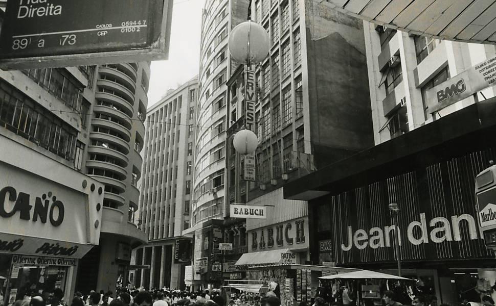 Uma rua paulista na década de 80. Uma placa escrita Direita no canto superior esquerdo (com 89 a 73). Lojas dos dois lados da rua e muitas pessoas circulando.