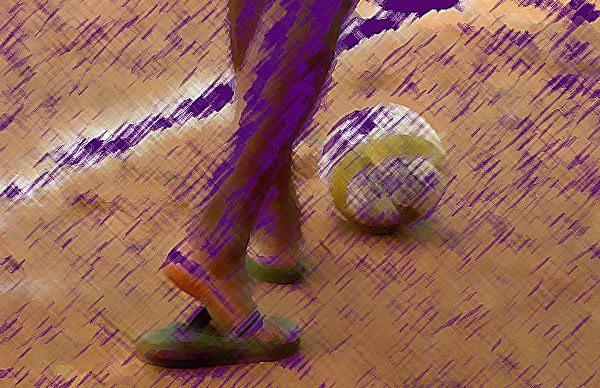 Visão de duas pernas de um menino usando chinelos chutando uma bola em um campo de terra batida. A imagem aparece borrada
