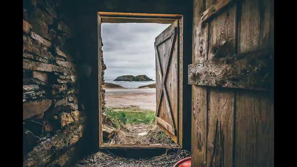 Um muro com uma porta aberta de madeira no final. Além da porta tem uma paisagem de areia e mar com umas rochas no fundo.