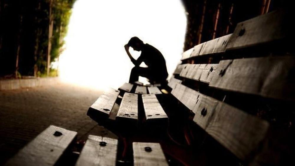 A silhueta de uma pessoa sentada em um banco de praça de madeira. Na imagem tem três bancos de madeira e a silhueta está sentada na mais distante. O cenário é de um trilha de floresta com um luz ao final.