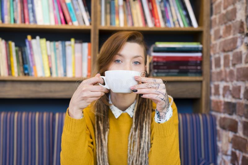 Uma menina ruiva de olhos azuis e suéter amarelo está com uma xícara de chá perto da boca como se estivesse bebendo. Está sentada em um sofá com listras azuis e amarelas. Ela aparece só do busto para cima. Ao fundo tem uma estante com livros.