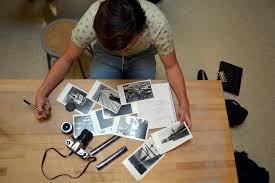 Uma visão de cima de uma mesa de trabalho de um fotógrafo. Várias fotos espalhadas por uma mesa de madeira com a máquina colocada no centro da mesa. O fotógrafo é visto de cima observando as fotos e fazendo anotações. Está vestido com uma blusa verde com algumas manchas indefinidas e uma calça jeans. Tem um banquinho de madeira ao fundo.