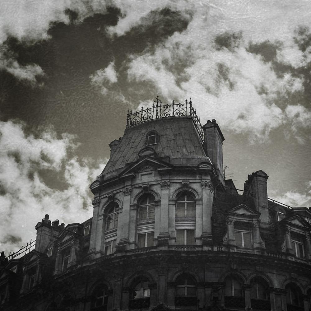 O topo de uma mansão gótica em um fundo preto e branco. Representa o instituto de estudos.