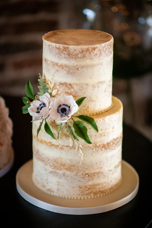 Semi naked wedding cake with anemones