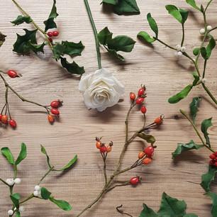 White rose, rose hips, mistletoe and holly flat lay arrangement