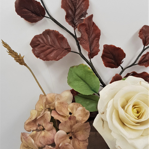 Close up of fading hydrangea, ivory rose and copper beech
