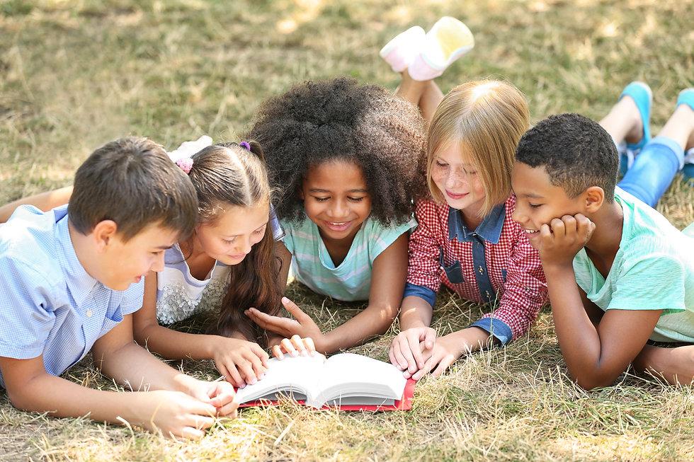 Cute kids reading book on green grass.jp