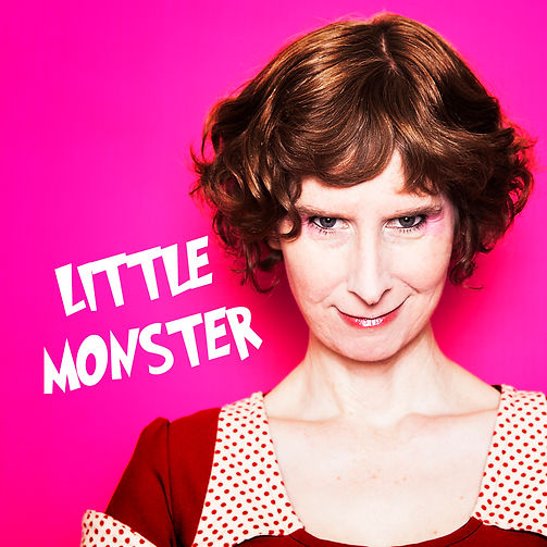 Telia Nevile, a woman with short, red curly hair, smiles menacingly at the camera. The words 'Little Monster' are on the left.
