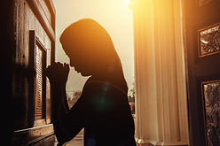 silhouette of woman kneeling and praying