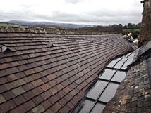 New stone slates replace the old, defective slates on this church roof.  The stone slates were cut and hand dressed to follow the slope of the new lead valley.
