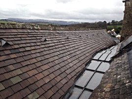 New stone slates replace the old, defective tiles on this church roof.  The stone tiles were cut and hand dressed to follow the slope of the new lead valley.