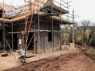 The stone coursework at the bottom of the building is complete, with the blockwork on top.  Windows are yet to be fitted, and the roof is starting to go on.