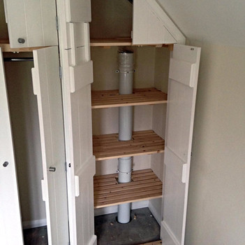 A bespoke airing cupboard was made to fit around an exposed boiler pipe, and other useful cupboards were made to utilise the rest of the space.