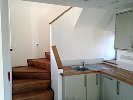 Bespoke stairs next to a compact, fitted kitchen create a smart look for this office.