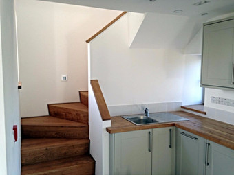 The compact kitchen next to the bespoke stairs.