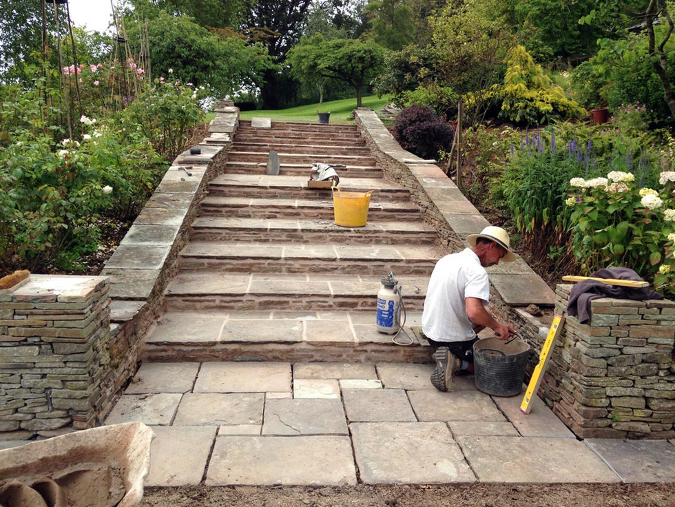 Stone pillars, walls and steps create a grand entrance to the garde