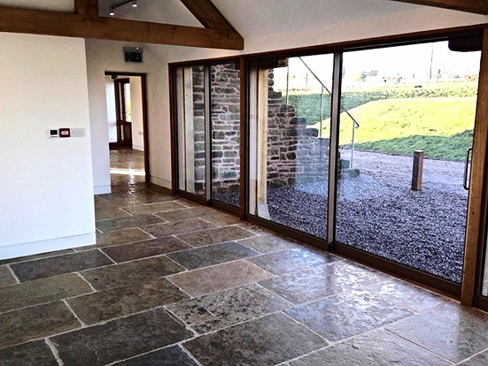 The natural stone tiles, exposed beams and huge glazed panels create a stunning interior that retains the rustic charm of the original barn.