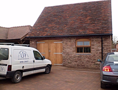 This garage was converted from a derelict outbuilding.  Here you can see repaired and re-pointed stonework, complete with brick arches.