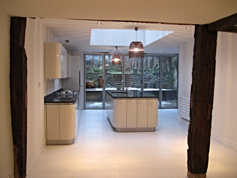 Pendant lights combined with roof lights and the glazed wall, ensure that there is plenty of light in this kitchen space.