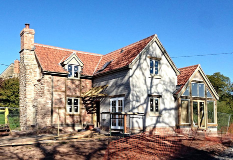 The renovated property taking shape.  You can see the brick and timber panels to the left and the oak and glass extension on the right that give the property an updated, rustic feel.