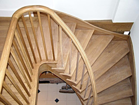 This curved oak stairs was custom made to fit the awkward space in this building