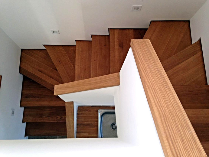 A bespoke, wooden staircase leading to the upper floor.