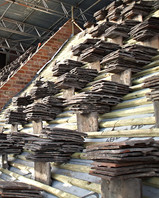 Plain clay tiles stacked, ready to be laid during a large re-roofing project.