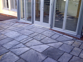 Beautifully laid patio which slopes up to the door.