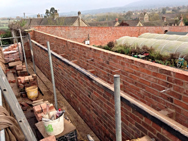 An old, derelict wall was repaired and areas of it replaced using reclaimed bricks that matched the existing wall.
