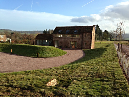 The driveway sweeps around this barn conversion, shaping the landscape, but blending into the surrounding countryside.