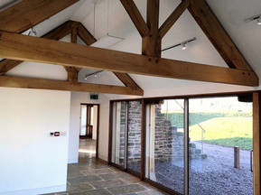 The sliding glass doors create a stunning source of light for this barn conversion.  The oak trusses are a fundamental part of the roof structure.