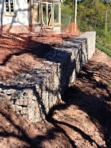 Stone gabions create a retaining wall on which to build