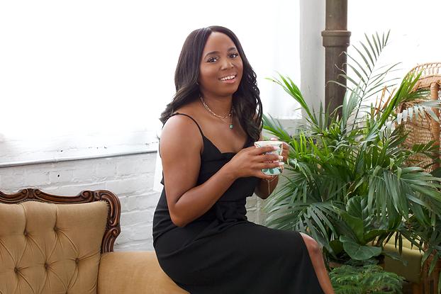 Karima Williams sitting on chair in black dress drinking tea