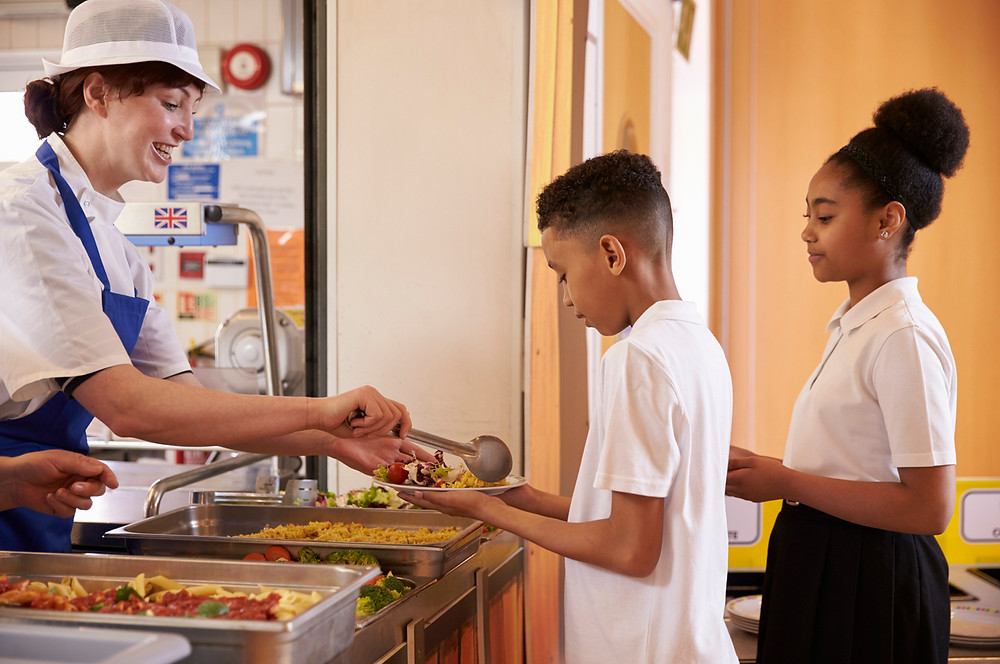 Woman serves students food in a school cafeteria.