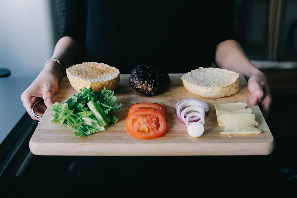 Zutaten für einen Fleischburger auf einem Holzbrett angerichtet