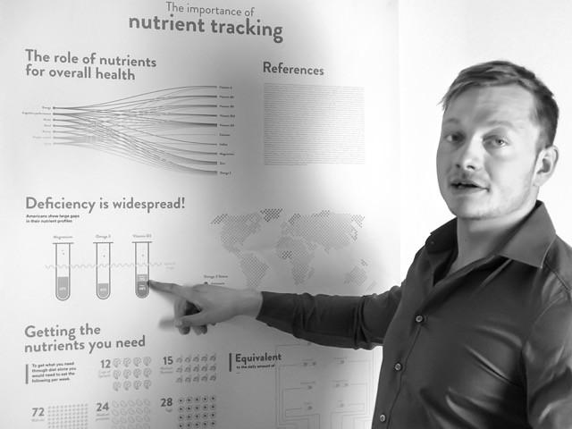 Mann zeigt auf ein Poster: Simon Goedecke - Nutrient-Information Scientist bei Baze