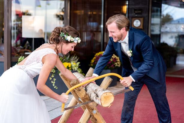 Hochzeitspaar beim Baumstamm sägen