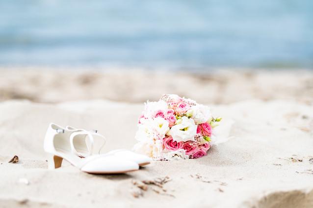 Brautstrauß und Brautschuhe am Strand