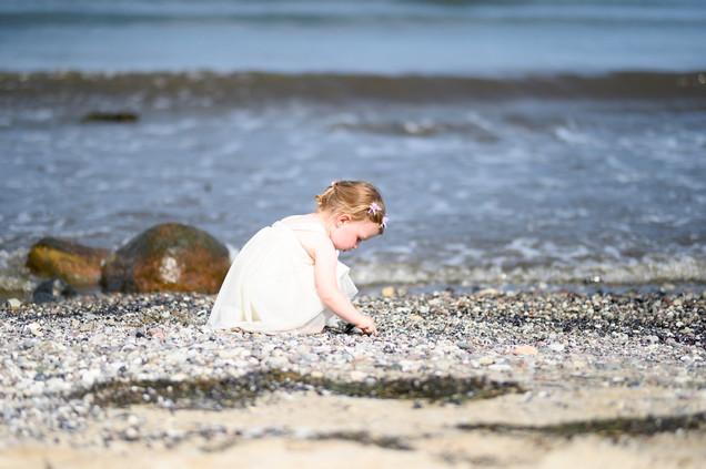 Kind am Strand mit Hochzeitskleid