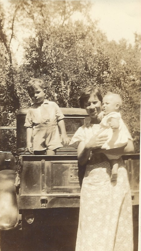 Ella Vae holding her youngest Joel; Jimmy's in the back of the truck