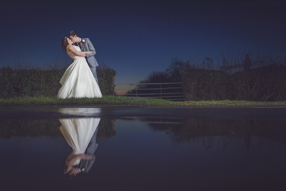 A newly wed couple kiss at in the evening light reflected back by the water outside the Ashbourne Hotel, North Killingholme, Immingham
