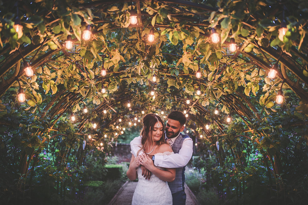 A nearly married couple hug under an archway lit by small lights