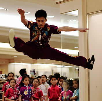 Advanced Wushu student leaps high in the air as the young students look up in awe!