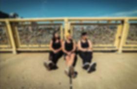 Sam, Tanner, and Karly from Broken to Barbell sitting against Roberto Clemene Bridge