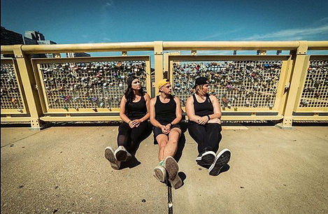Sam, Tanner, and Karly from Broken to Barbell sitting against Roberto Clemene Bridge