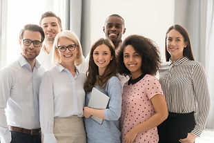 Multiethnic smiling businesspeople standing looking at camera making group photo in office