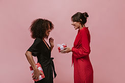 Trendy brunette lady with silver round earrings in red bright dress giving gift her curly ...ox..jpg