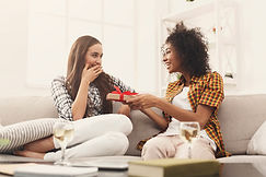 Excited woman getting gift from her girlfriend. Two happy female friends exchanging presen...ace.jpg