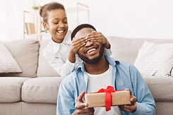 Father's day. Happy daughter congratulating dad and giving present at home.jpg