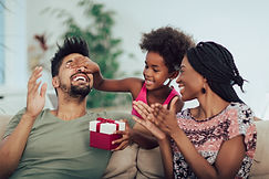 Happy black family at home. African american father, mother and child celebrating birthday...th..jpg